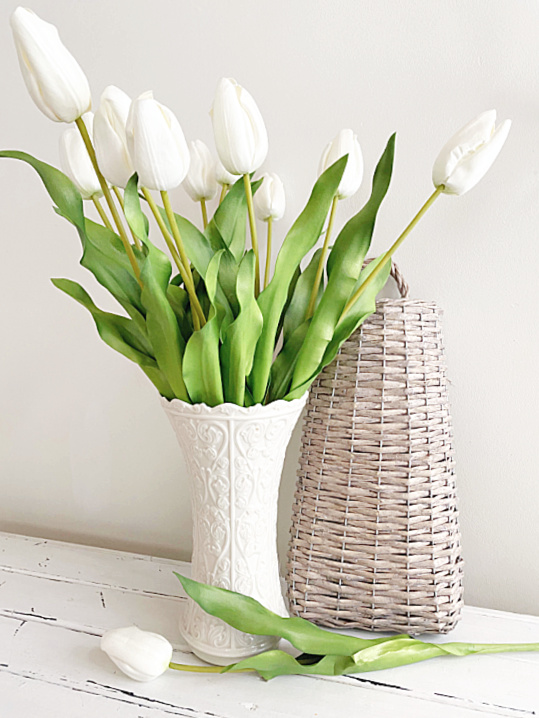 white tulips in a white vase with a basket