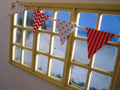 Modern one-twelfth scale miniature window overlooking the beach, with red and white bunting strung across it.