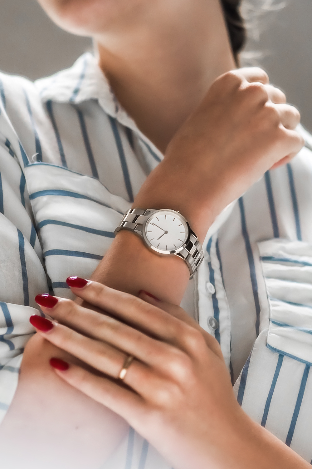 a close-up picture of a woman's hand with a silver watch on it