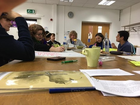 The Brain Charity research team sat around a table analysing Antonia's story and portraits. Some people are talking and some are writing.