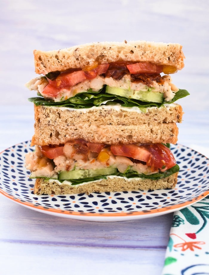 An italian white bean sandwich stacked high with lots of fillings