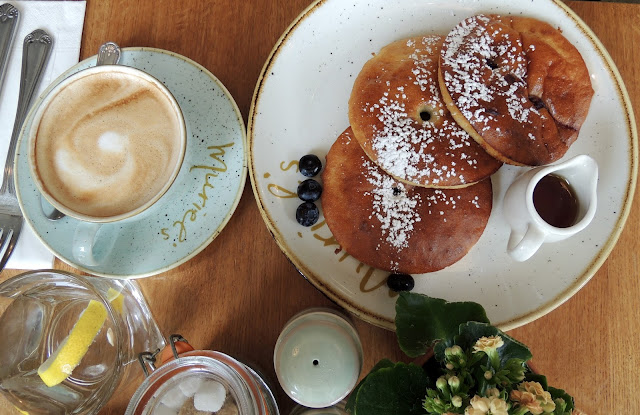 cappuccino and pancakes with blueberries and maple syrup