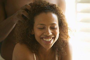 Mujer pelo afro recibiendo masaje capilar