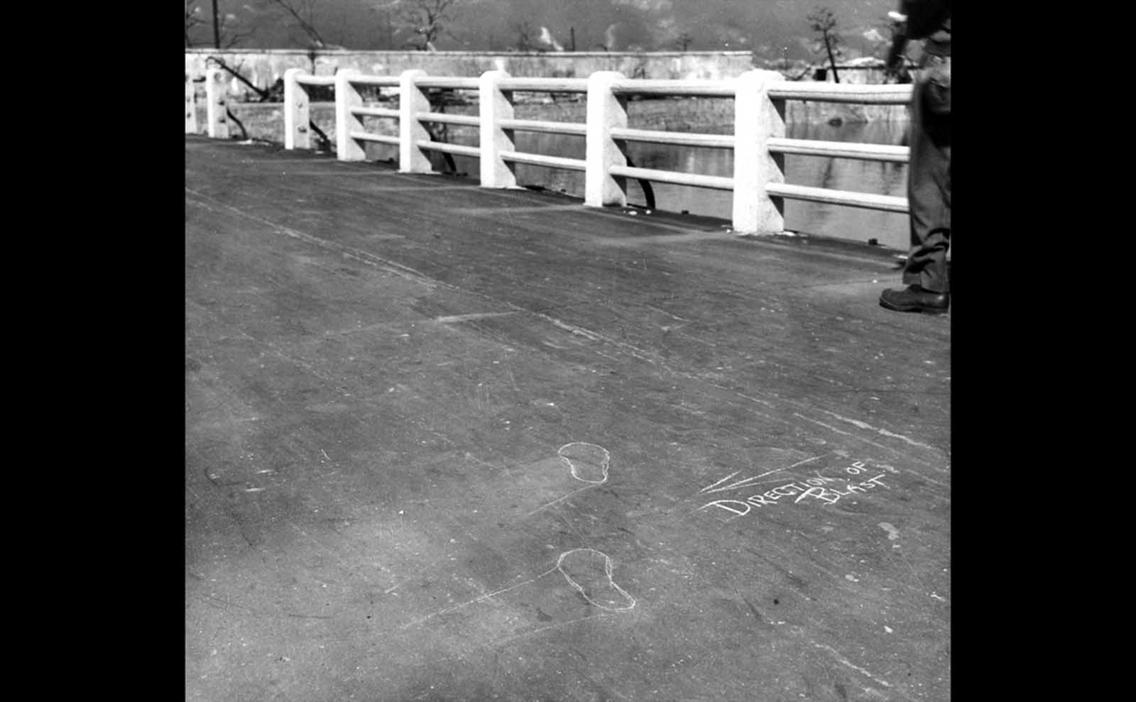 """""""Direction of blast"""" chalk marks and outlines of the feet of a victim caught in the explosion. The intense heat of the initial flash of the detonation seared every nearby surface, leaving inverted """"shadows,"""" like those seen on this bridge left by the railings and by a person who had been standing in this place."""