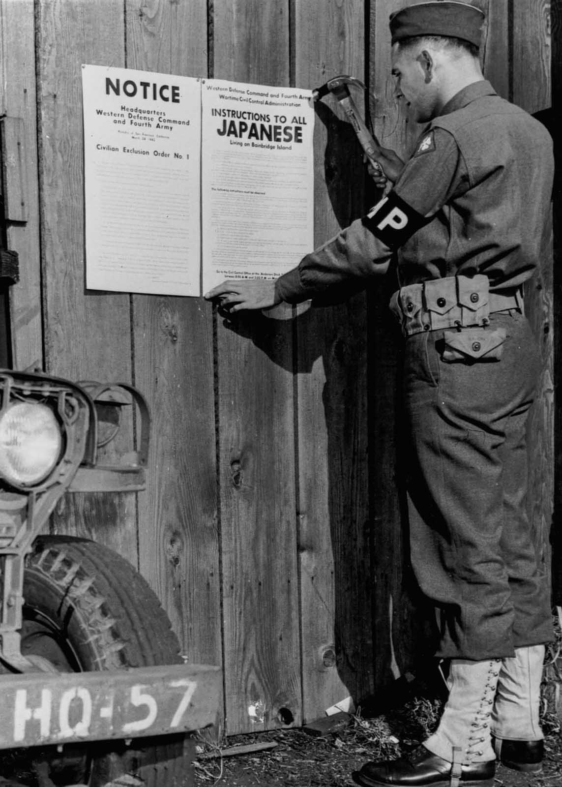 A military police officer posts Civilian Exclusion Order No. 1, requiring evacuation of Japanese living on Bainbridge Island, Washington.