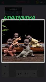 на столе стоят статуэтки чернокожих детей в разных позах