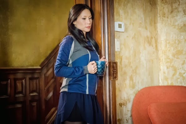 Lucy Liu as Joan Watson in a blue dress in NY brownstone in CBS Elementary Season 2 Episode 16 The One Percent Solution