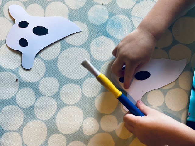 Really easy and simple ghost shapes with a child gluing the black eyes and mouth on