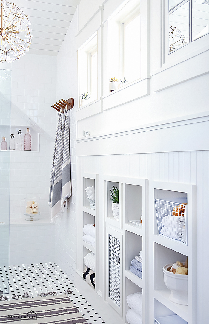 white bathroom with build in shelves under the eaves and framed little windows