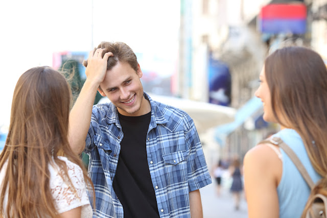 Young man speaking to two young women on the streets of Reykjavik
