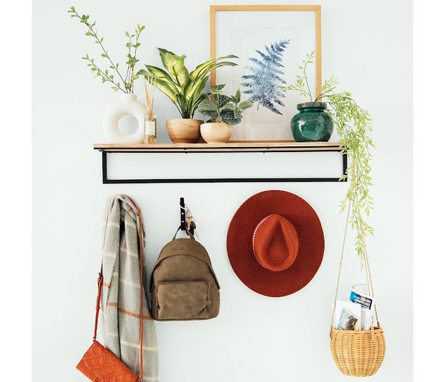 white modern donut vase on display with faux plants on entryway shelf