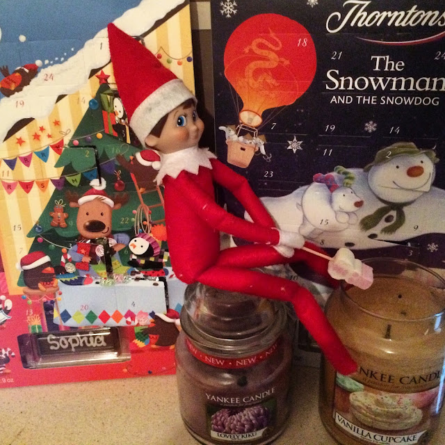 Elf on the shelf toasting a marshmallow on a stick on a candle