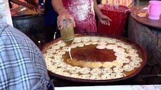 توضع الزلابية في الزيت بالقمع الخاص بها