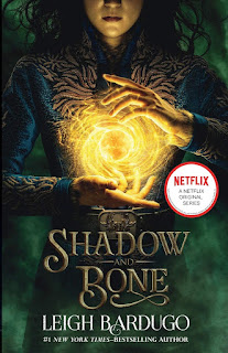 Image of the Shadow and Bone Netflix tie-in cover, featuring a girl with swirling sunlight held between her hands against a dark green background