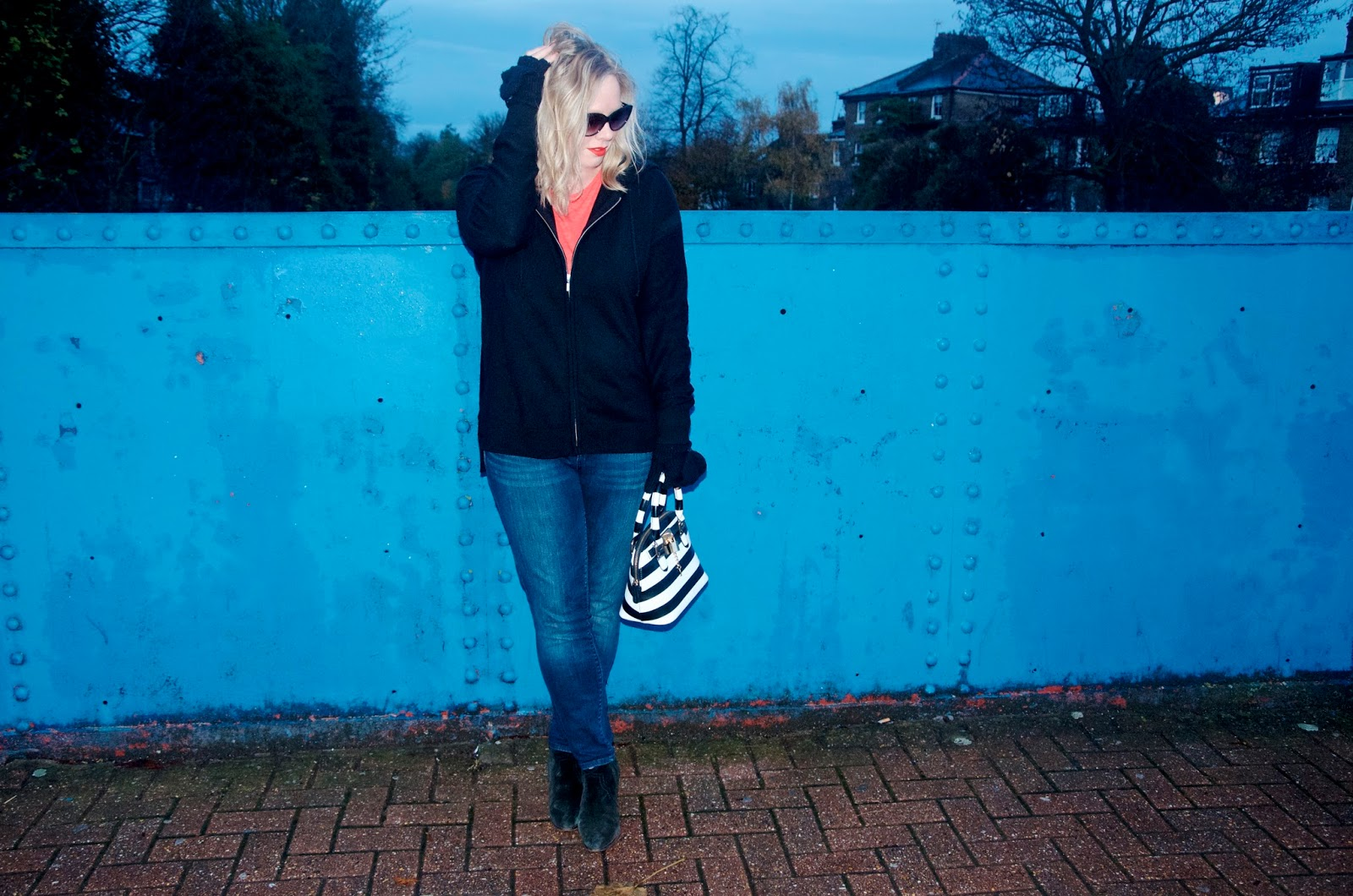 Black hoodie sweater and striped bag with blue bridge