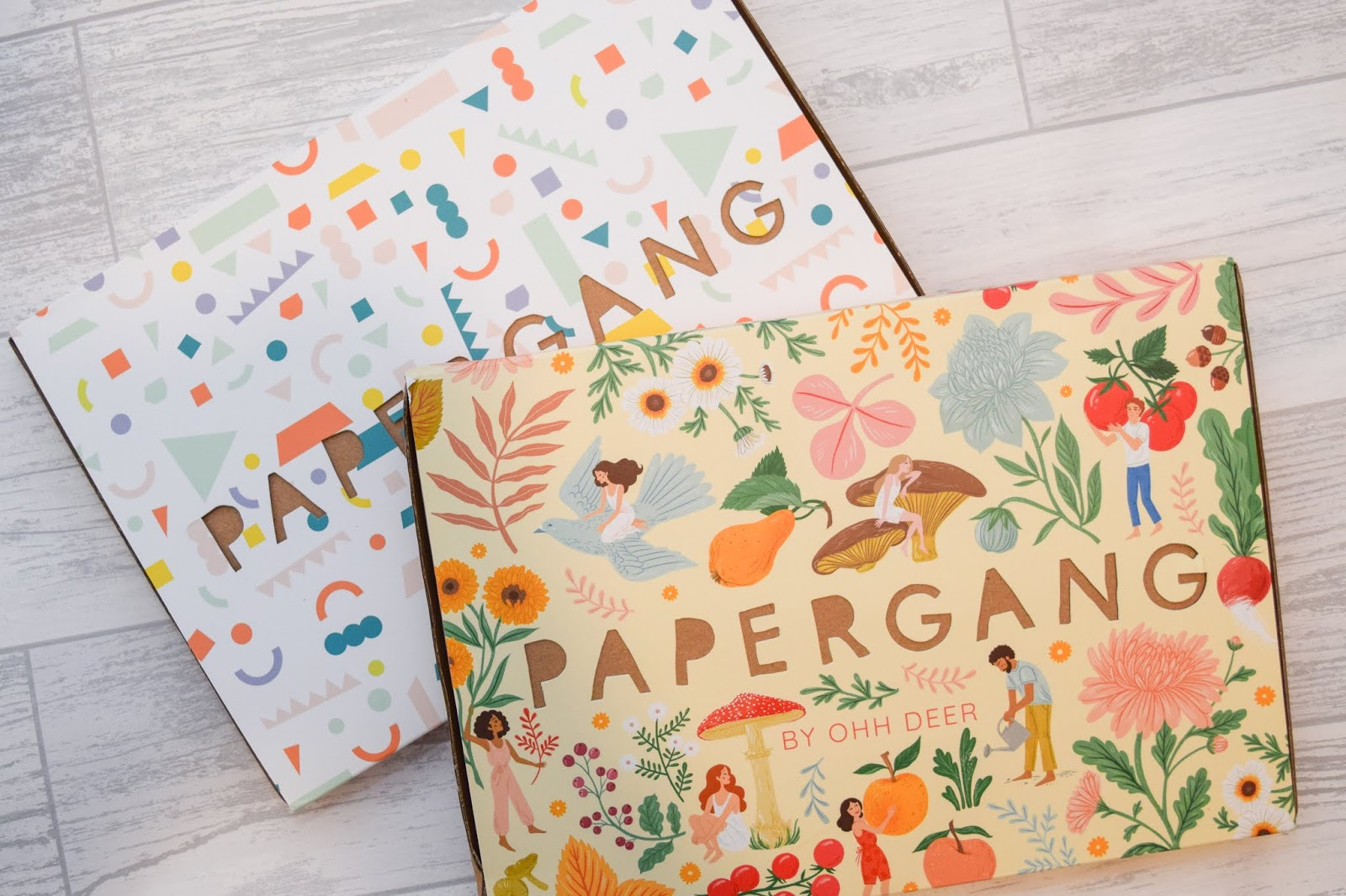 Two letterbox sized boxes with colourful prints on top stacked on a white wooden background.