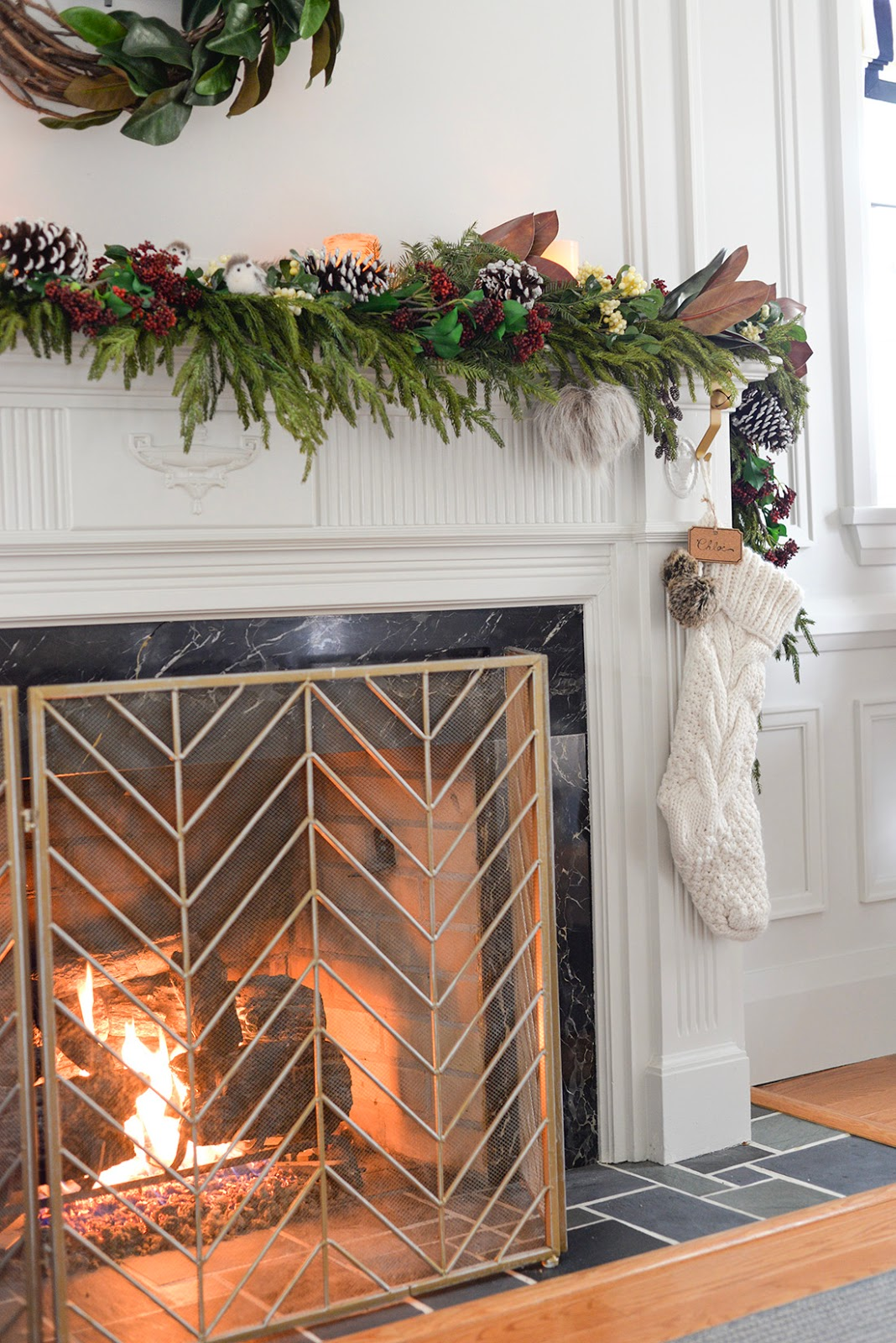 a faux christmas fireplace mantel garland with red seeded eucalyptus, a cedar garland and magnolia leaves. A vine and magnolia asymmetrical wreath with satin ribbon and metal bells. A brass chevron fireplace screen.