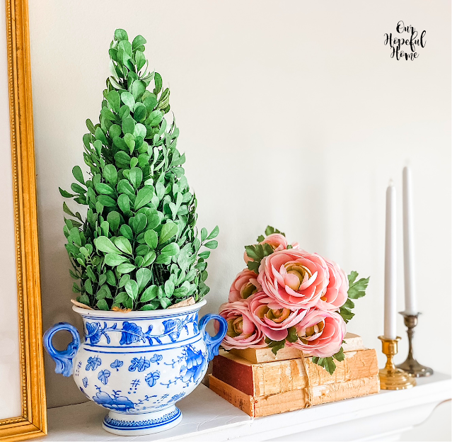 brass candlesticks blue white pottery boxwood flowers