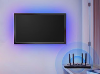 Tv on the wall with a purple glow coming out of it, connecting to a router in the front of the image