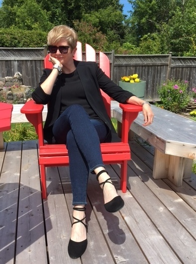 woman sitting in red Adirondack chair, wearing jeans, black flats and a black tank and jacket