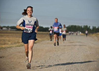 امرأة مع مريلة سباق على الركض مع العدائين الآخرين في الخلفية على طريق ترابي
