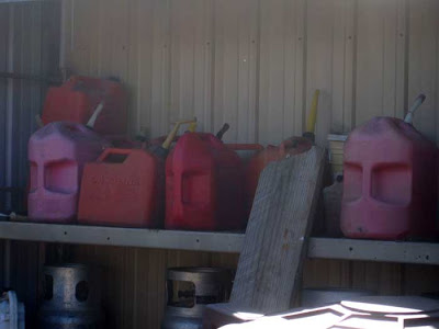 Pink and red plastic gas cans turned with their handles facing the camera, which makes them look like brooding, heavy-browed faces