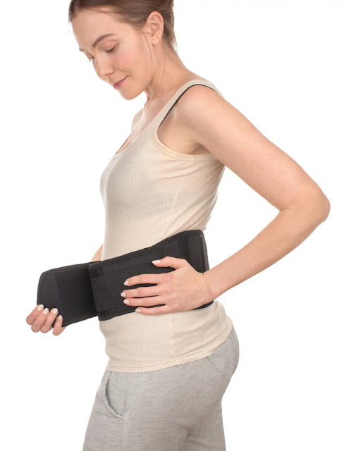 lower back center - woman-putting-wrapped-sports-medical-belt