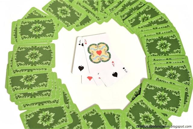na zdjęciu rozsypane w koło karty odwrócone koszulkami do góry, na środku leżą odkryte karty