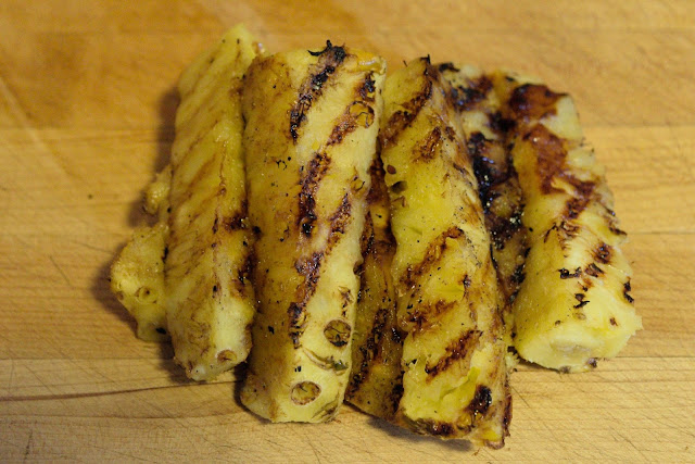 The grilled pineapple on a cutting board.