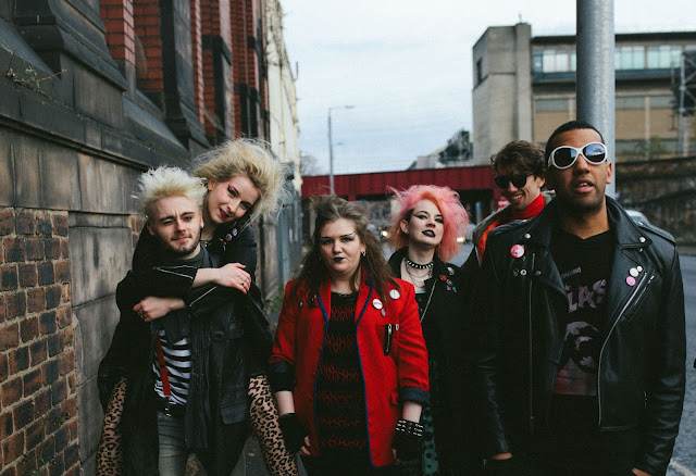 Photo of a group of young people walking down an industrial looking street. They are wearing punk inspired outfits.