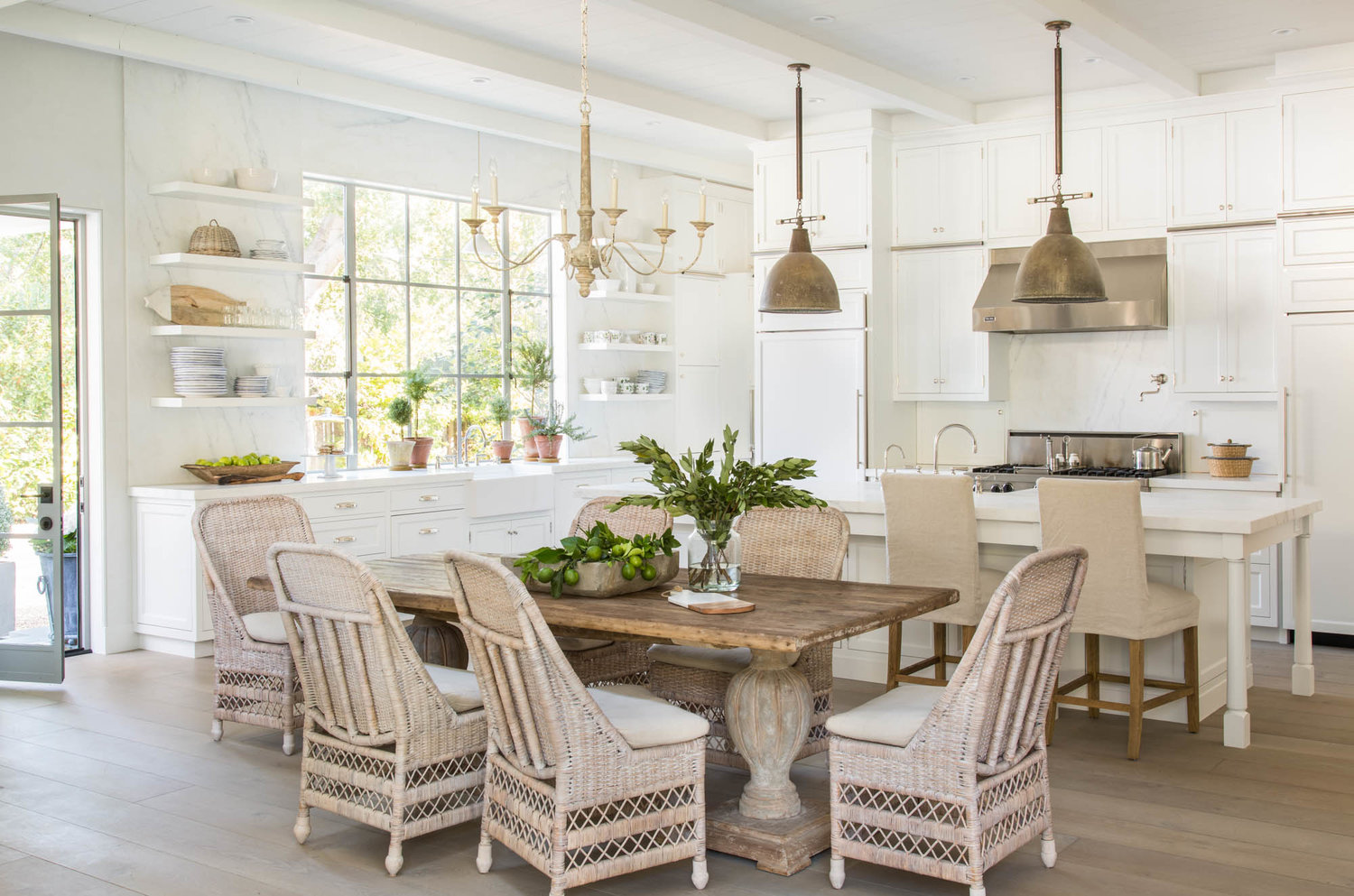 Modern farmhouse style in white kitchen and dining area with antique furnishings, open shelves, and French oak wood floors