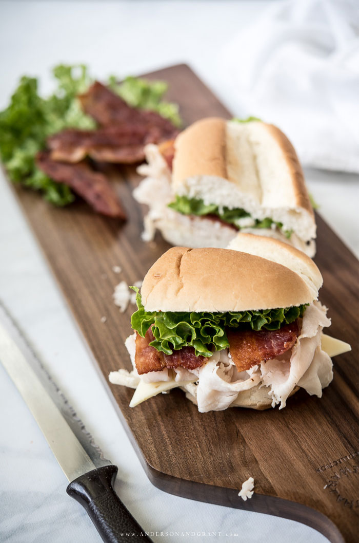 Cut turkey sub on dark wood board with knife