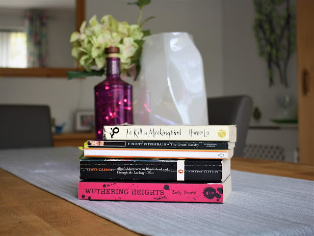 classic novels in a pile with flowers behind