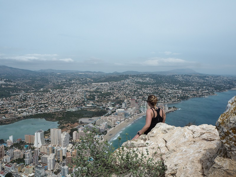 Woman with plaited hair sat on the rocks at Penon de Ifach's summit, looking out over Calpe