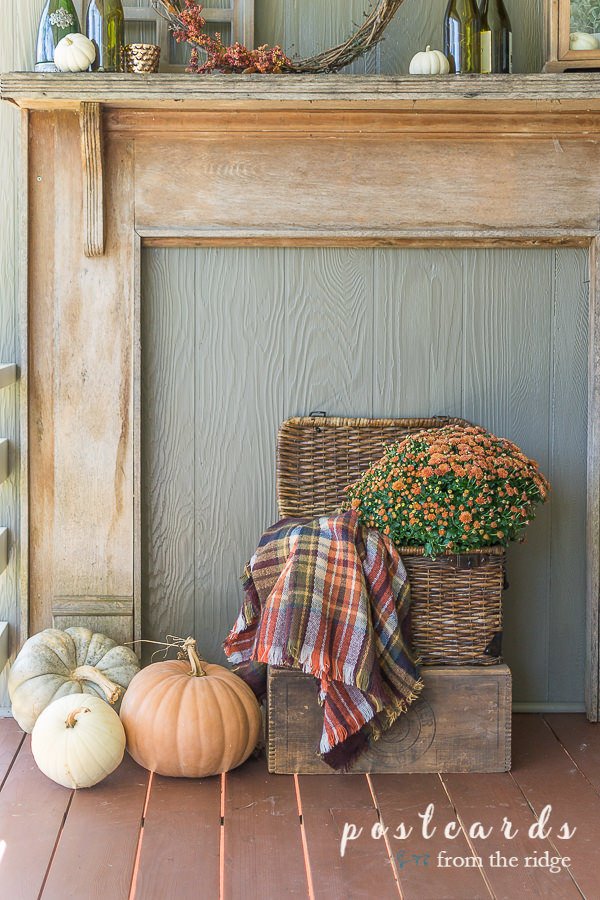 rustic fall mantel with fall decor and basket with plaid blanket scarf and mums