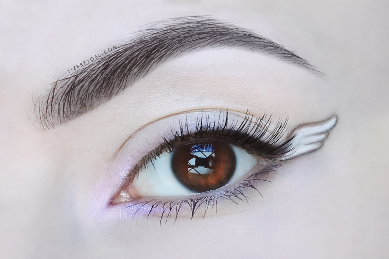 a close up picture of an eye with the angel wing eyeliner in the corner