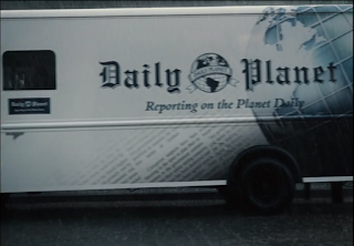 """A newspaper truck with the Daily Planet logo and the slogan """"Reporting on the Planet Daily."""""""
