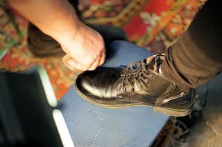 Membersihkan sepatu atau sandal.