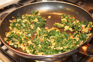 spinach and garlic and onion frying in pan