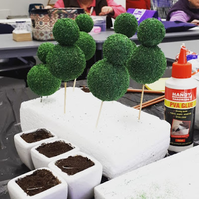 Six one-twelfth scale topiaries skewred to a piece of styrofoam next to four planters filled with miniature soil.