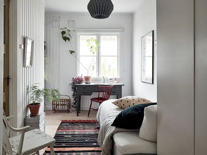Dormitorio de estilo nórdico con viejo escritorio pintado