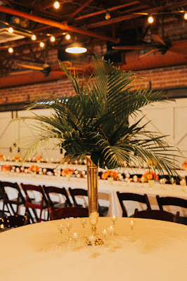 tall greenery centerpieces on gold vase