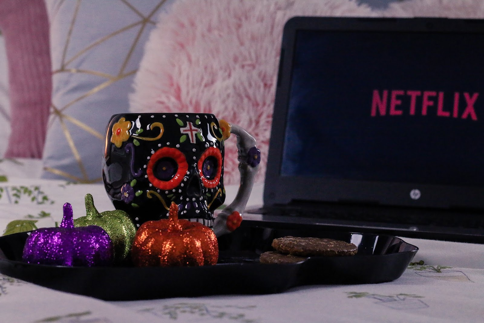 Extreme Close up of a sugar skull tea mug on a black skull tray with three pumpkin ornaments next to it, one orange, one green and one purple. The tray is sitting on a bed with a laptop in the background which is blurred as the mug is in focus, taken side on.