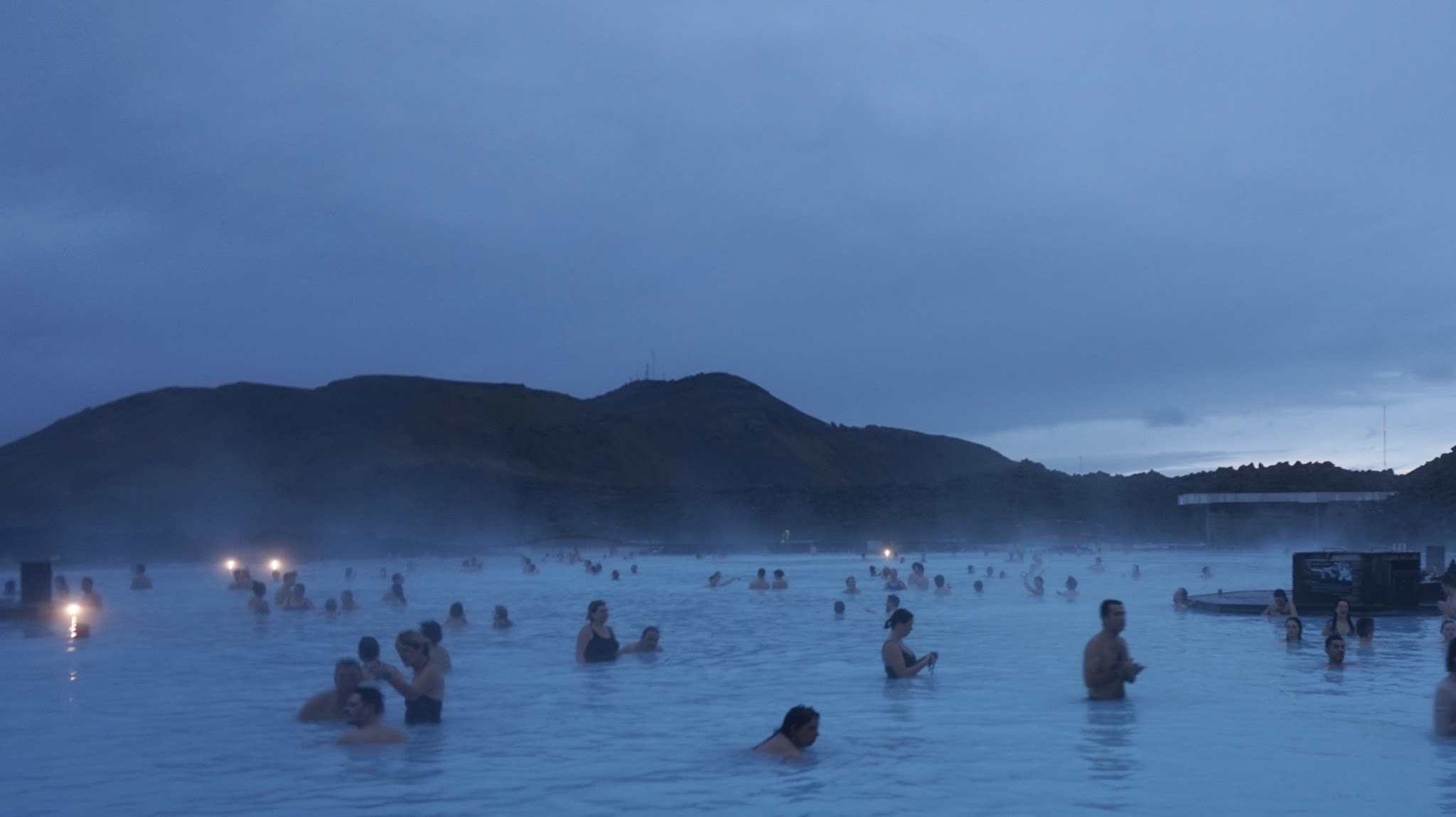 evening, lots of people swimming, steam rising off the water into the atmosphere