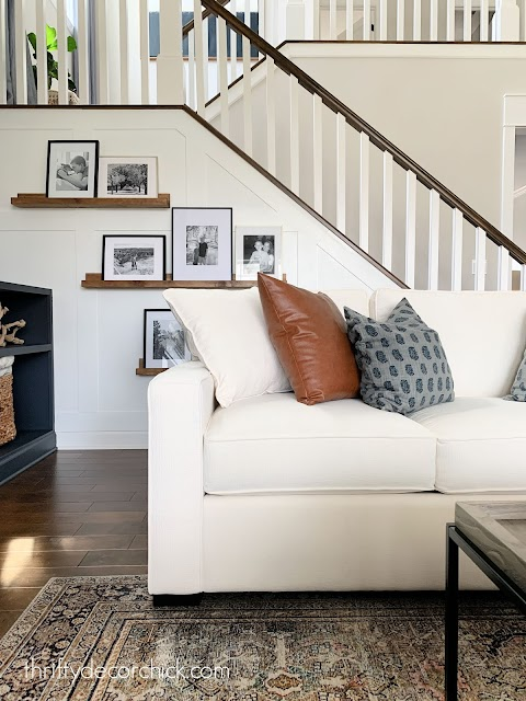 cream sofa with blue and leather pillows