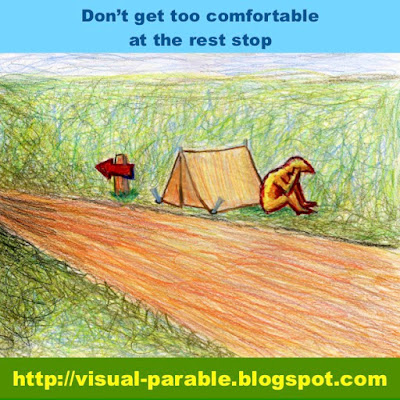 A man camping on the side of the road ignoring an obvious sign of direction.