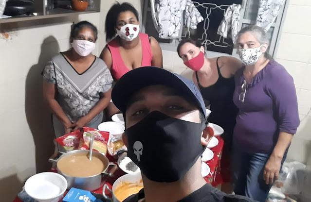 Pessoas reunidas em torno de mesa, usando máscara e preparando marmitas