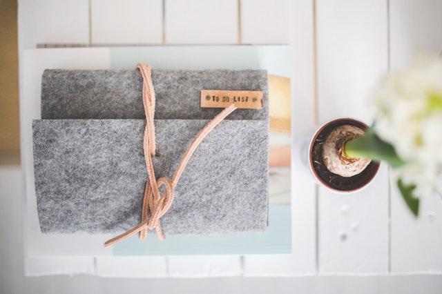 Cuaderno de fieltro gris sobre un escritorio con un florero al lado