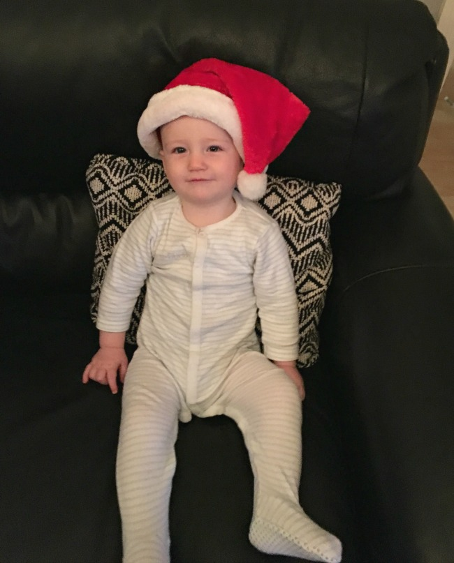 Christmas-gift-guide-2018-secret-projects-secret-piloow-in-black-and-white-on-sofa-with-baby-wearing-santa-hat