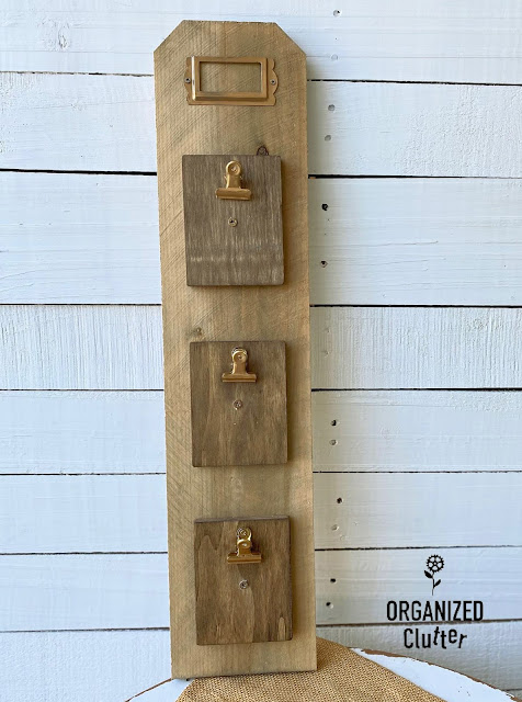 Photo of stained fence board with 3 mini clipboards and a metal tag frame